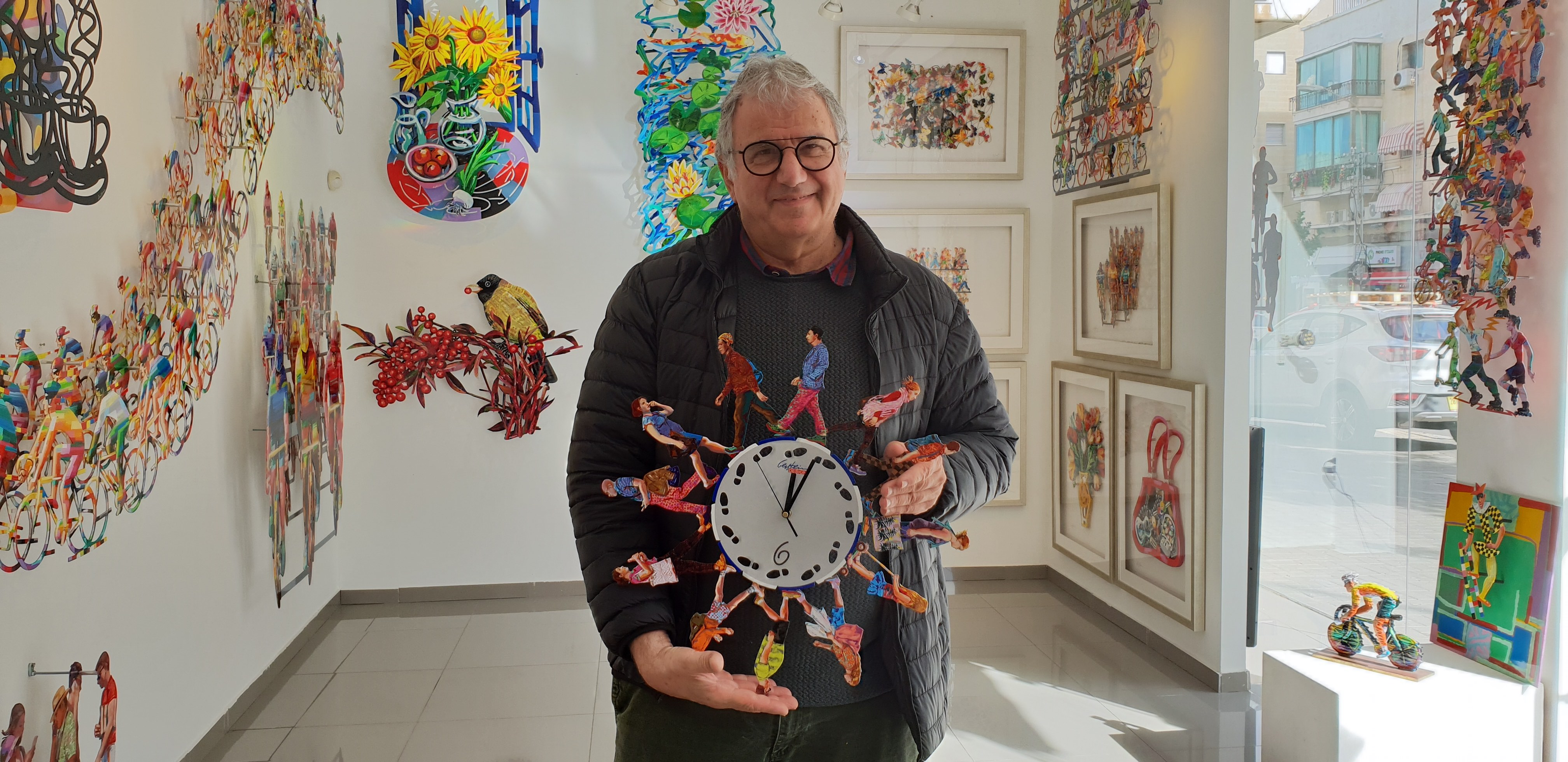 Artist David Gerstein holding his Walkers Time Clock at Gerstein gallery in Tel Aviv